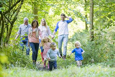 Family With Three Young Kids On An Outdoor Trail